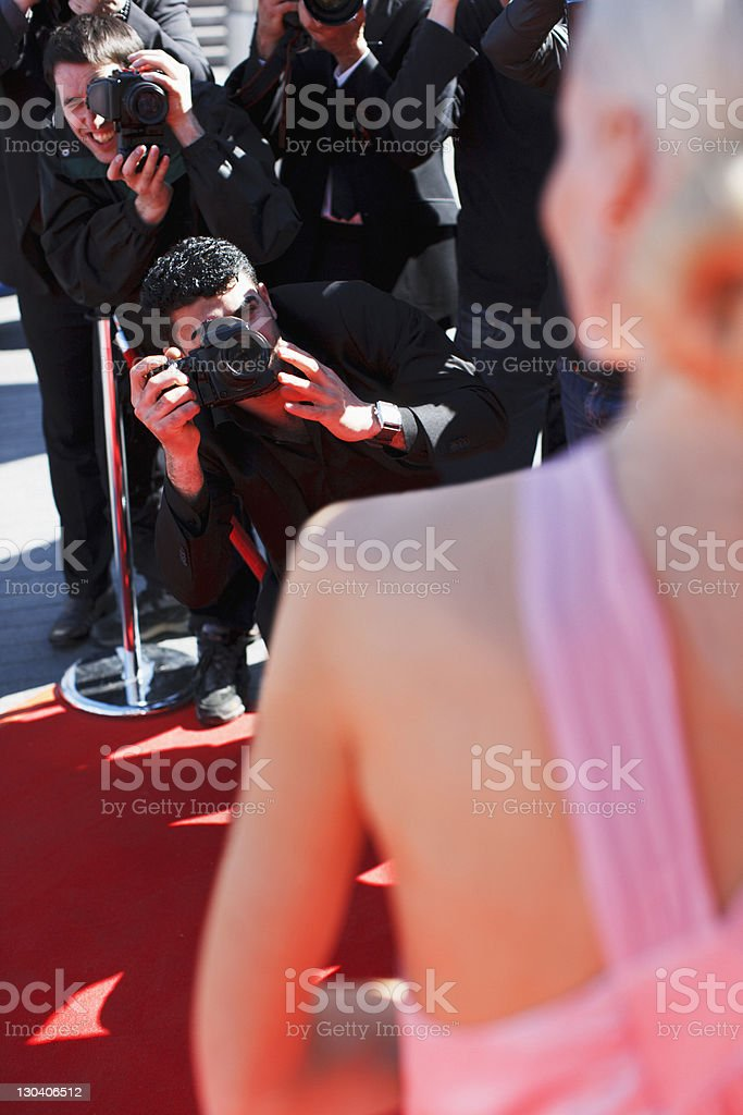 Celebrity posing for paparazzi on red carpet royalty-free stock photo