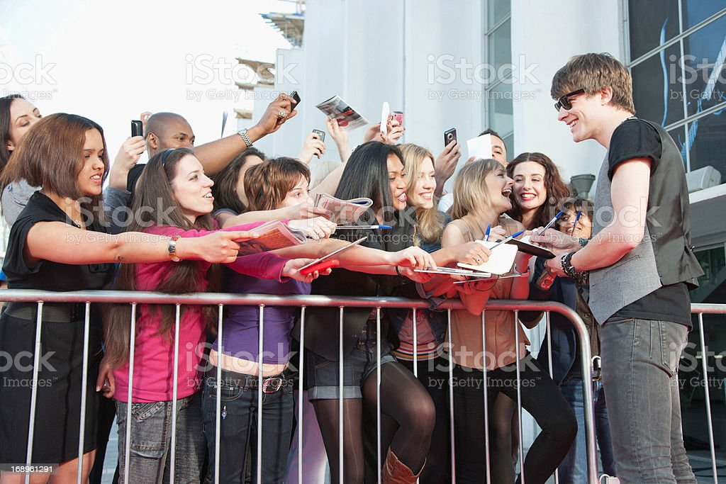 Celebrity signing autographs for fans stock photo