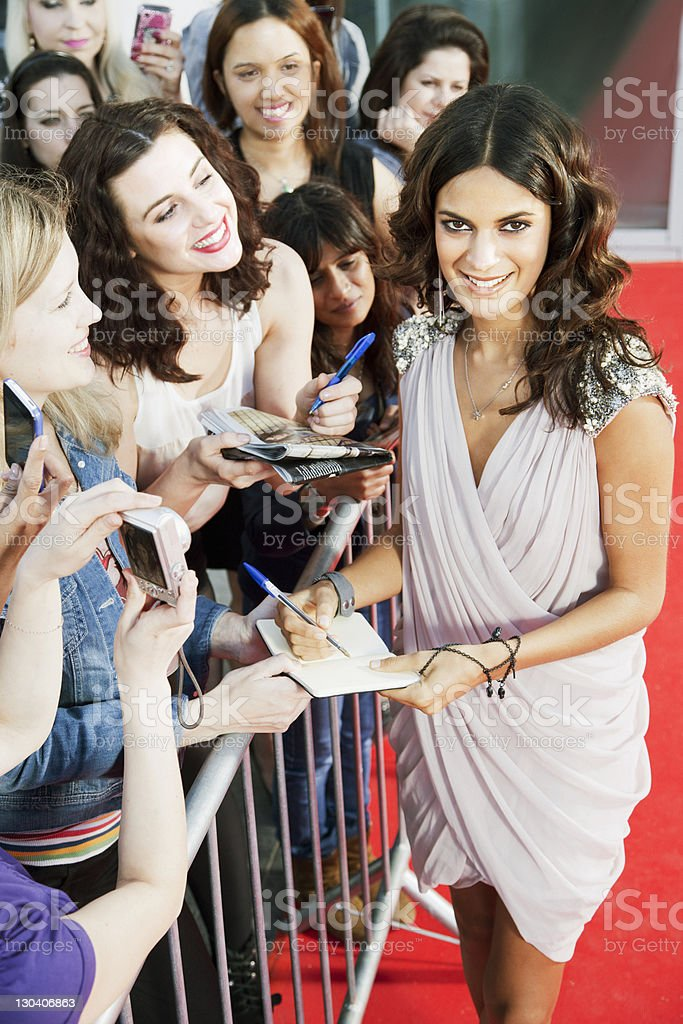 Celebrity signing autographs on red carpet stock photo