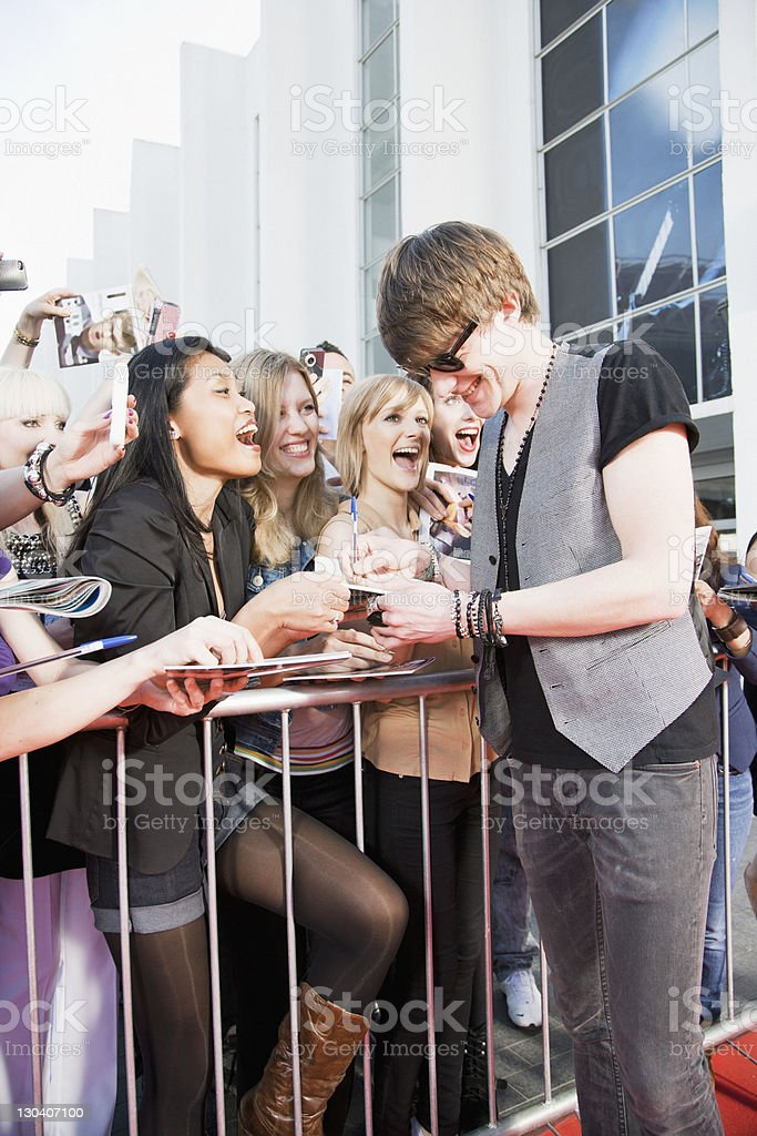Celebrity signing autographs on red carpet royalty-free stock photo