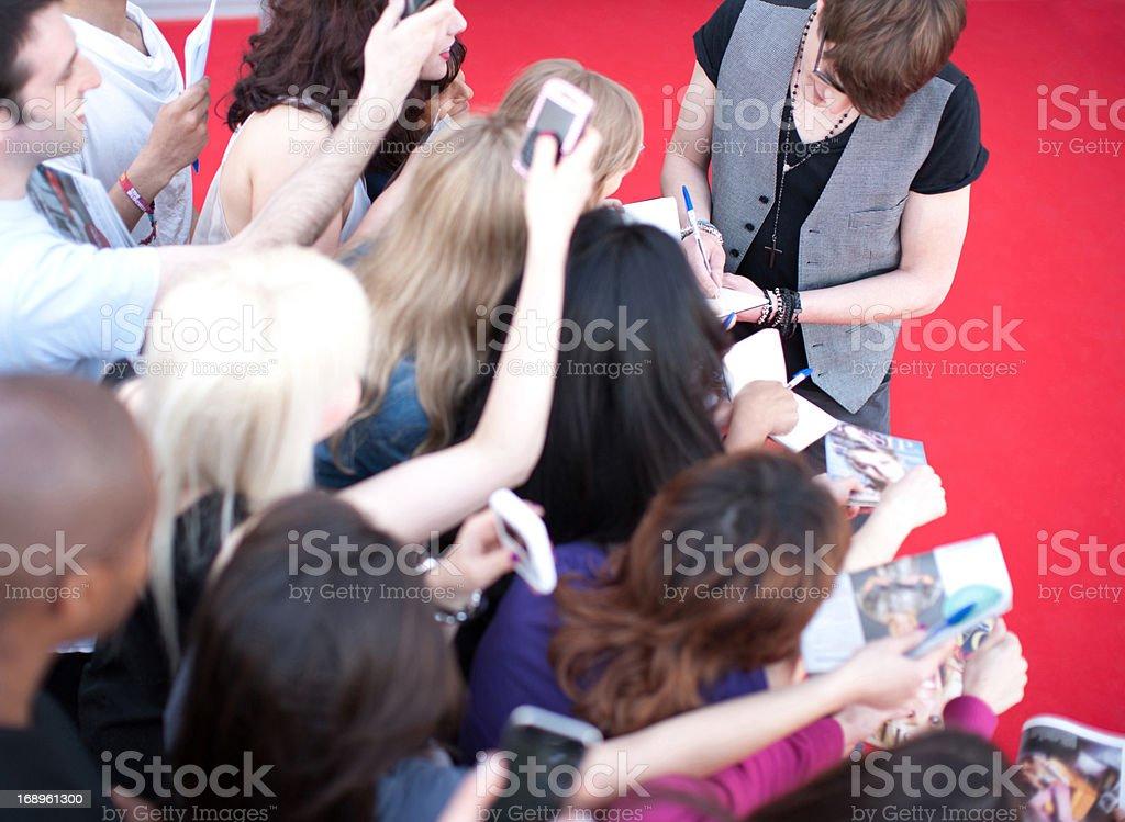 Celebrity signing autographs stock photo