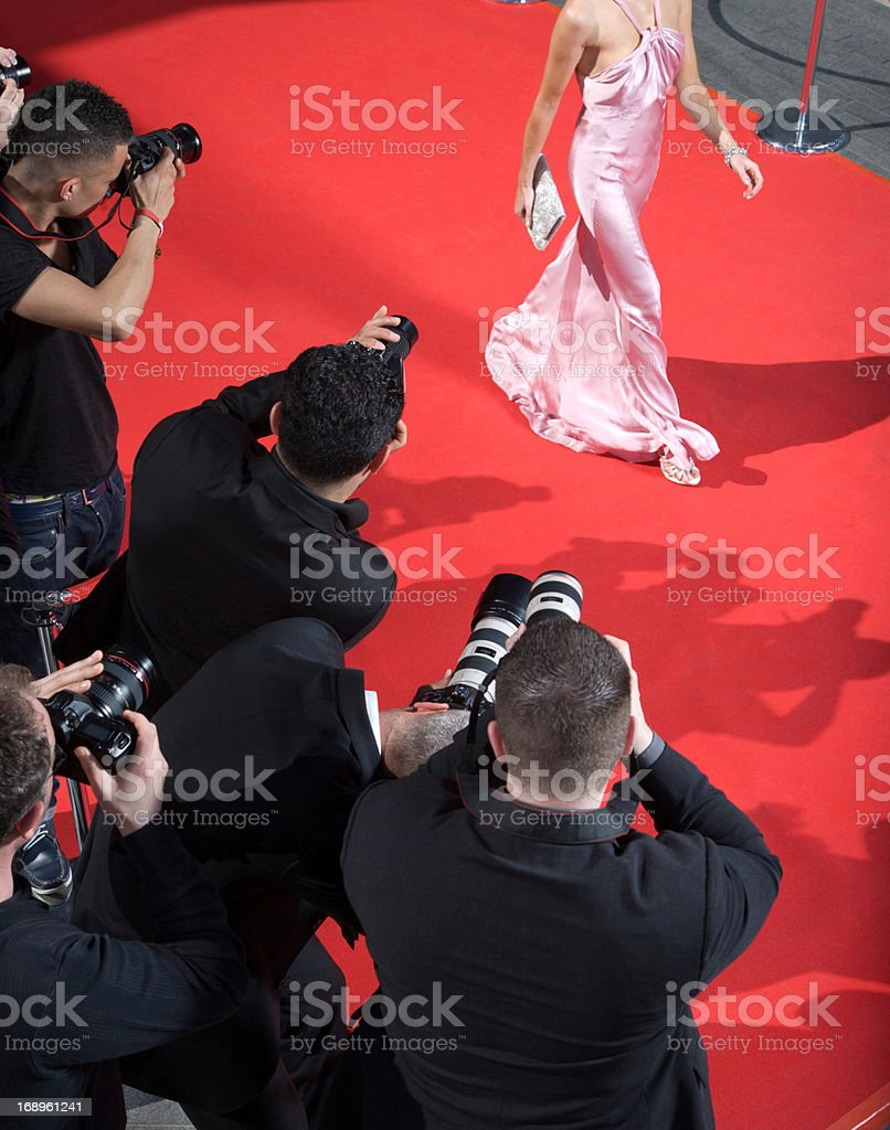Celebrity walking for paparazzi on red carpet stock photo
