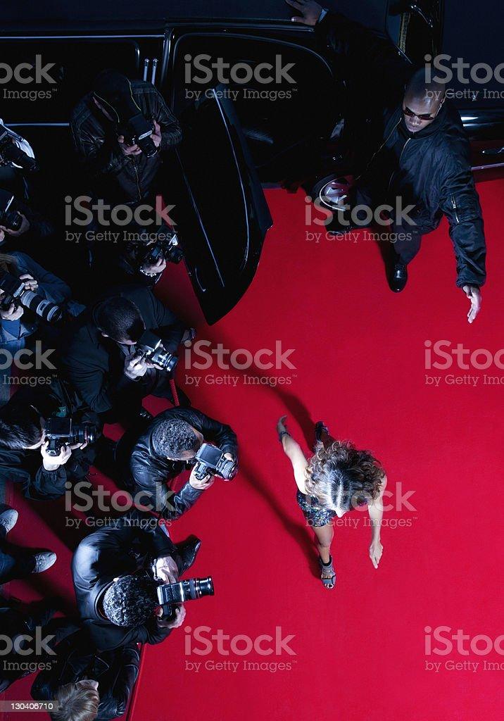 Celebrity walking past paparazzi on red carpet royalty-free stock photo