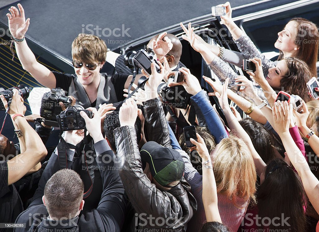 Celebrity waving to paparazzi and fans stock photo