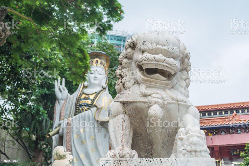Celestial lion statue and Kwun Yam statue at Kwun Yam temple. stock photo