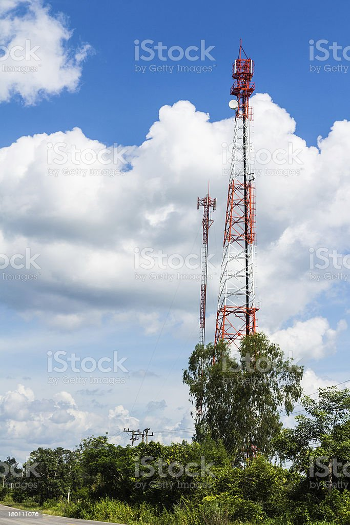Cell phone and communication towers against blue sky royalty-free stock photo