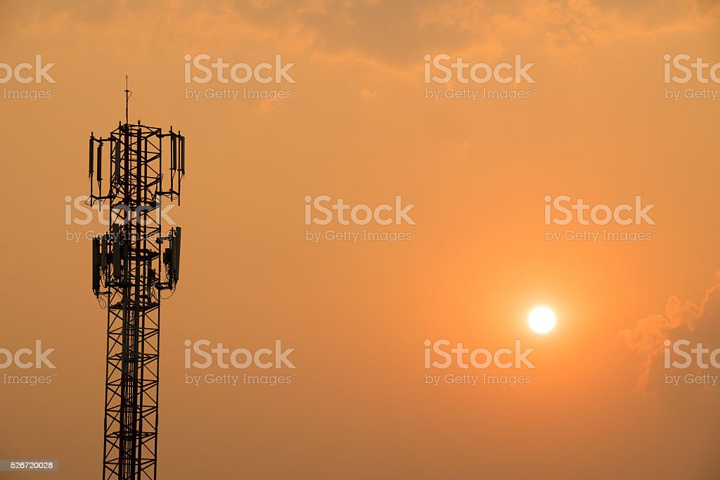 Cell Phone Antenna Tower on orange sky and sun stock photo