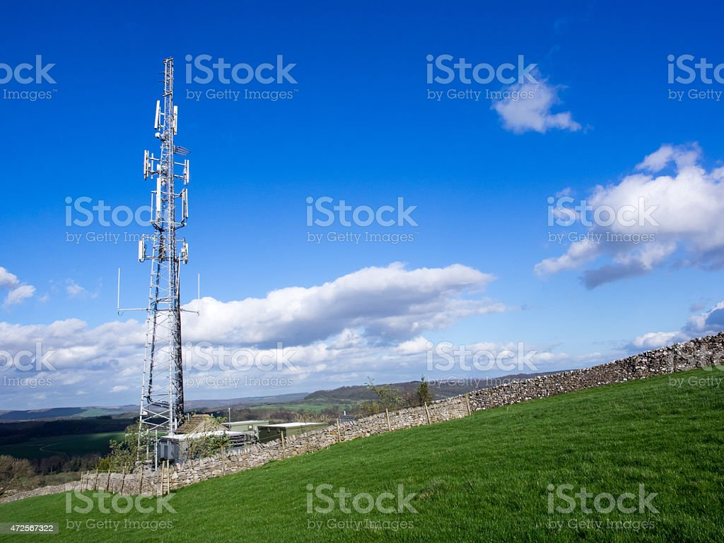 Cell phone communication mast in green field stock photo