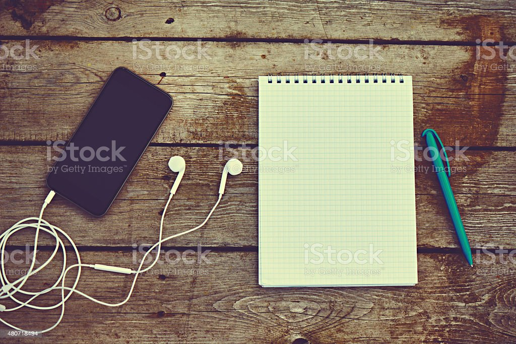cell phone, headphones, notebook and pen on old wooden table stock photo