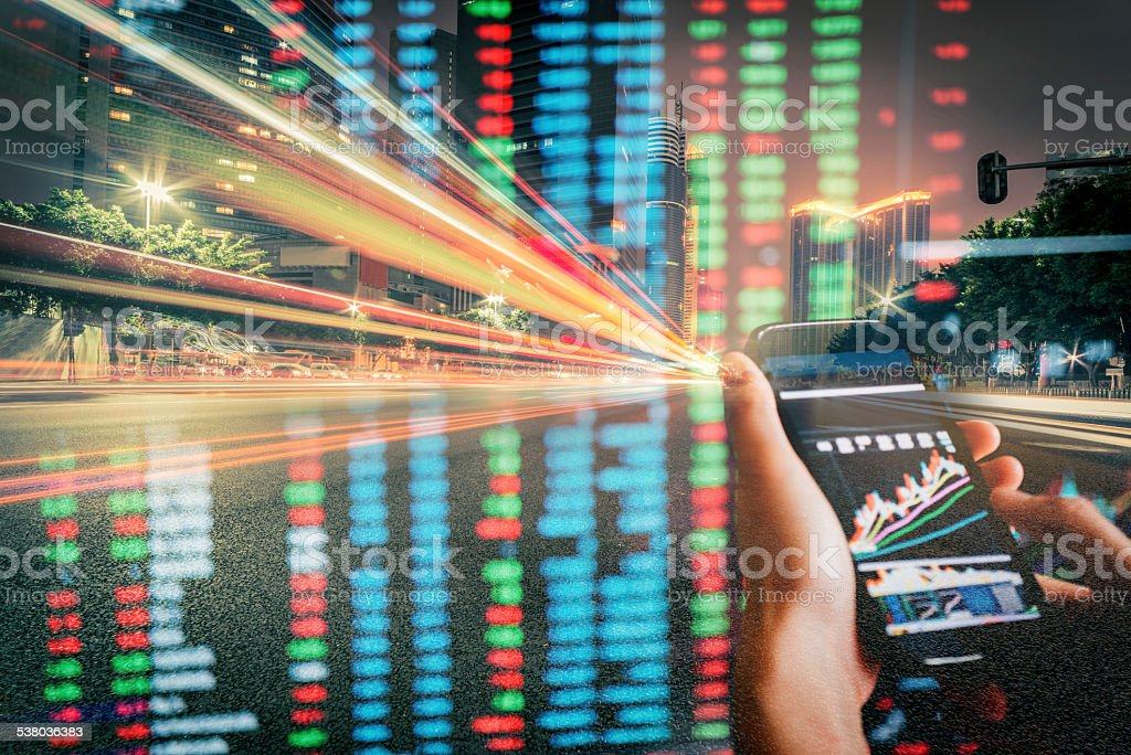 cell phone on hand with stock market data business concept stock photo