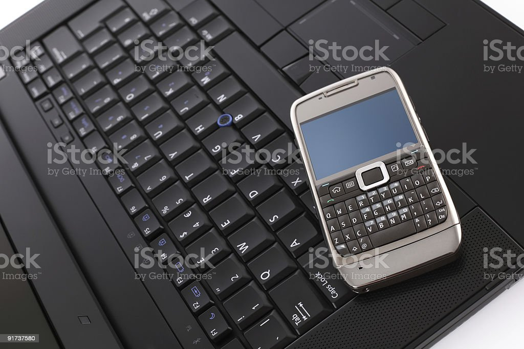 Cell phone on laptop computer stock photo