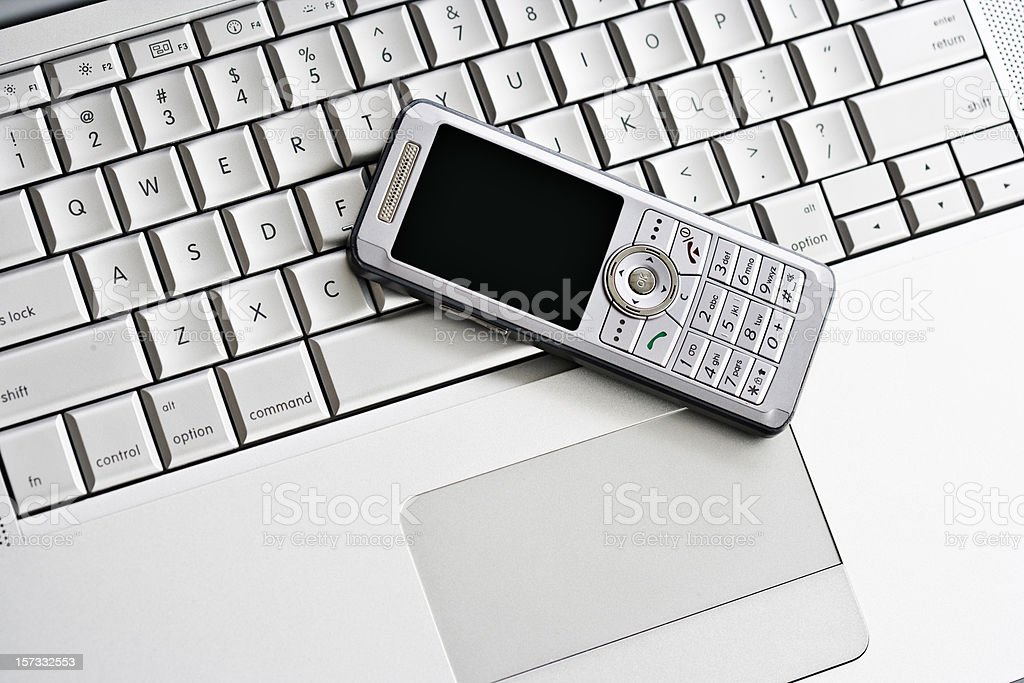 cell phone on metal keyboard royalty-free stock photo