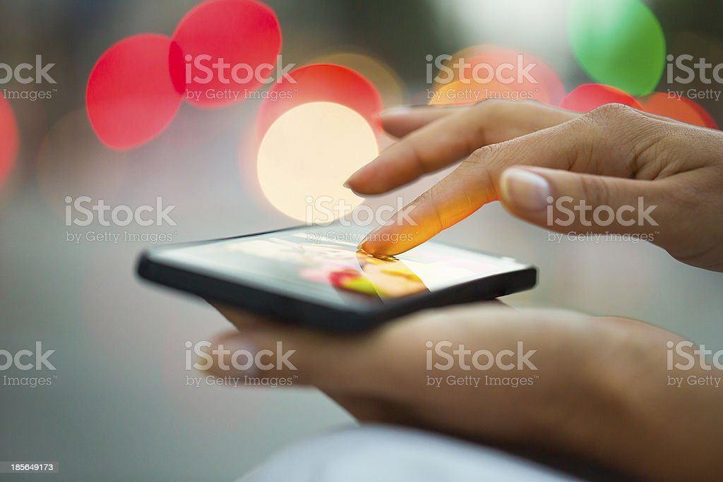 Cell phone in a woman's hand, city of Lights background stock photo