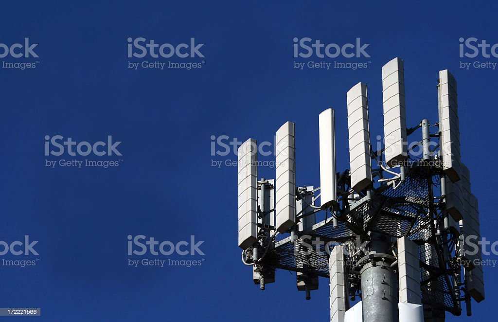 Cell tower standing in the blue sky stock photo
