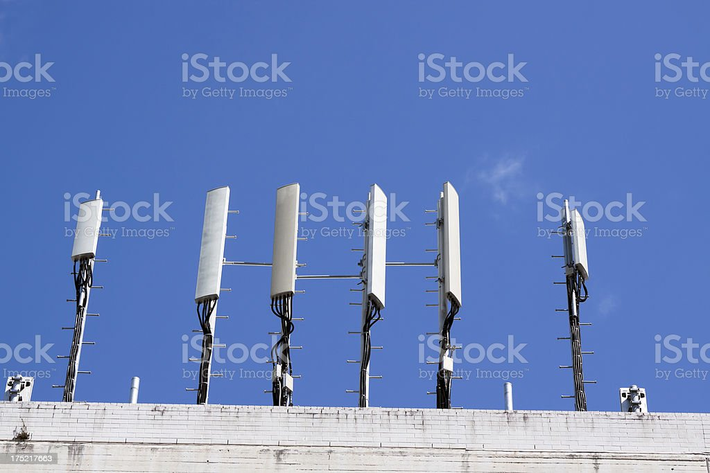 Cell towers on top of building, blue sky, copy space stock photo