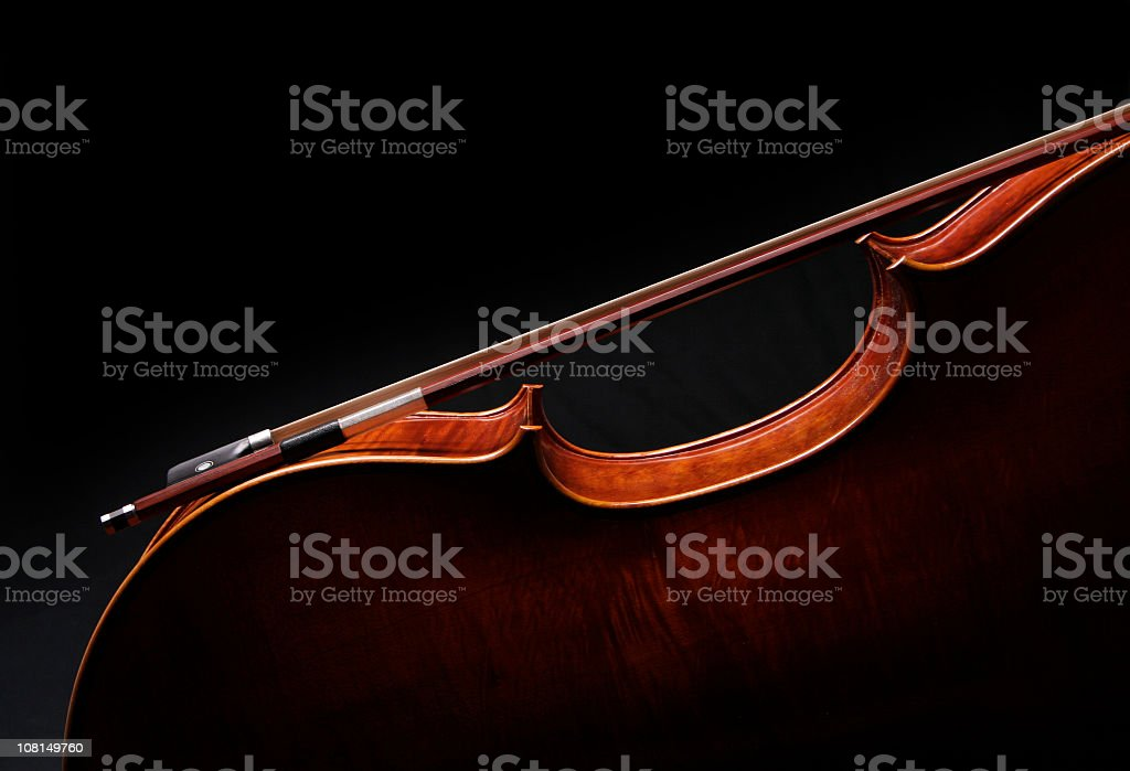 Cello silhouette with bow on black background royalty-free stock photo