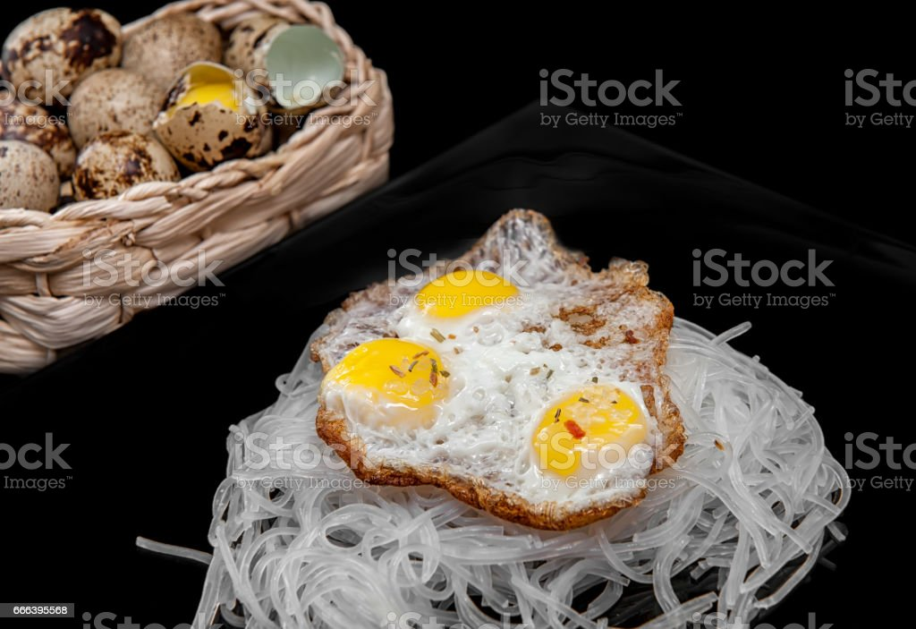 cellophane with scrambled quail eggs with eggs in a basket in the background, on a black background stock photo