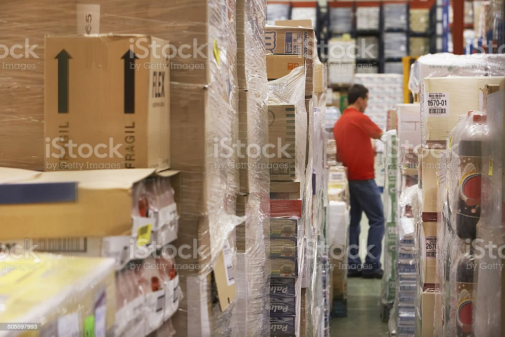 Cellophane Wrapped Goods With Man In Background At Warehouse stock photo