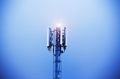 Cellphone tower shining into the evening sky