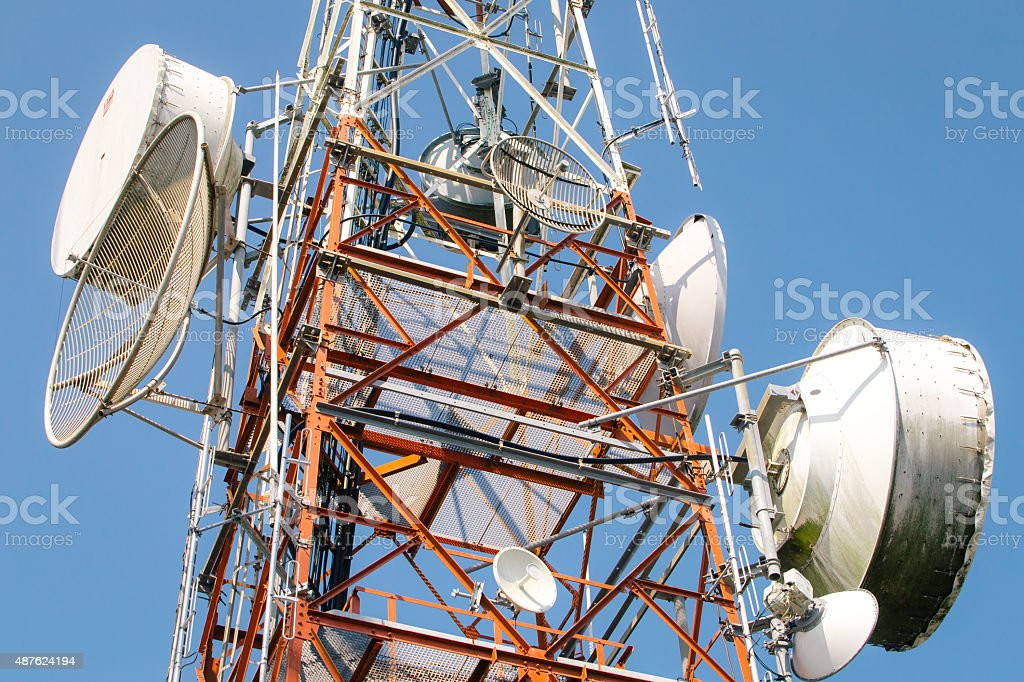 cellular communication towers on blue sky stock photo