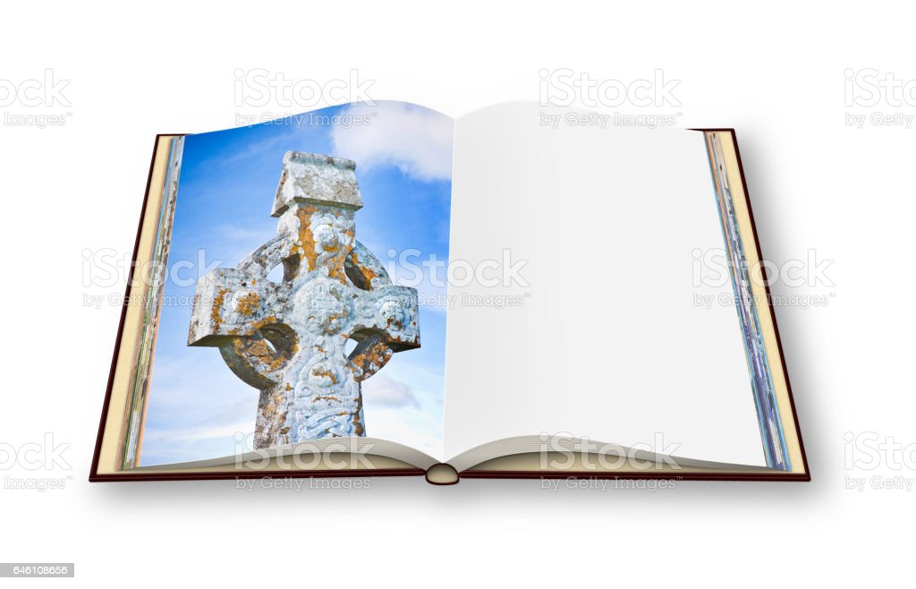 Celtic carved stone cross on open photo book. stock photo