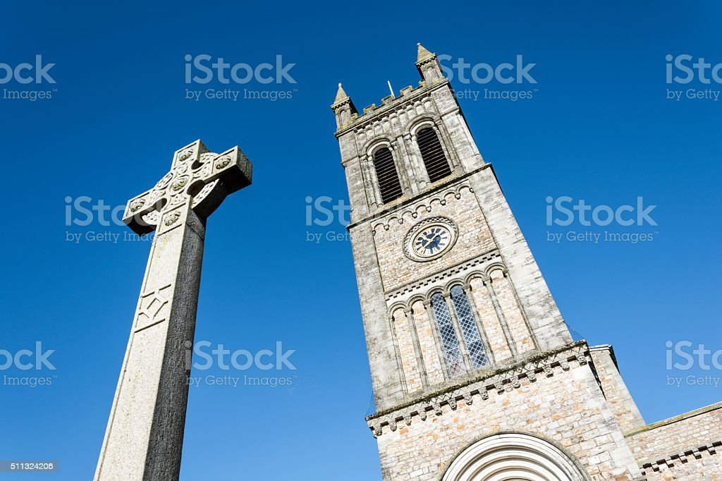 Celtic Cross and Church clock tower stock photo