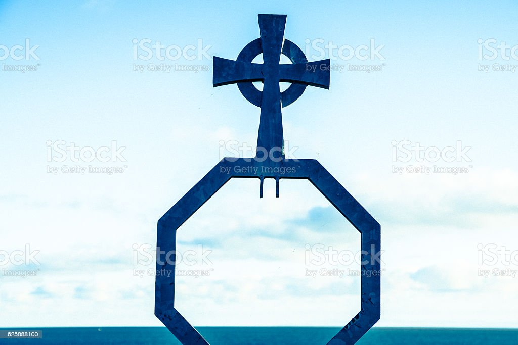 Celtic cross, blue tint, against sea horizon stock photo