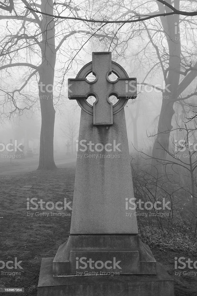 Celtic Cross in foggy graveyard royalty-free stock photo
