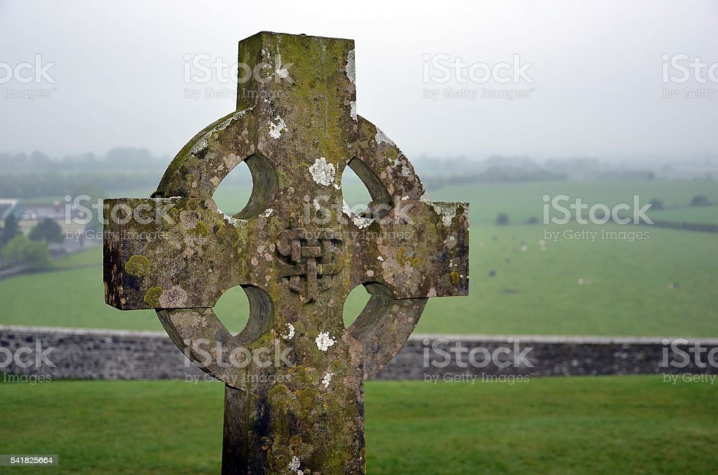 celtic cross on the graveyard and nature landscape stock photo