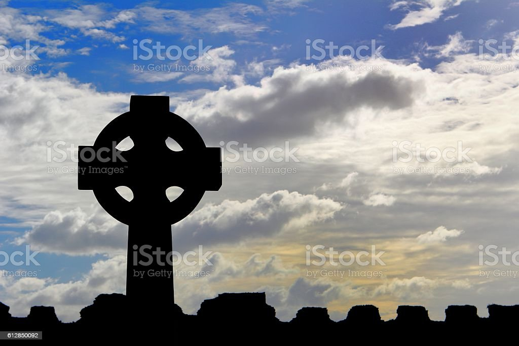 Celtic cross silhouetted against a dramatic sky stock photo