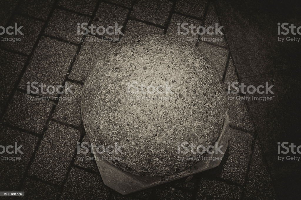 Black and white ground cement ball in an alley