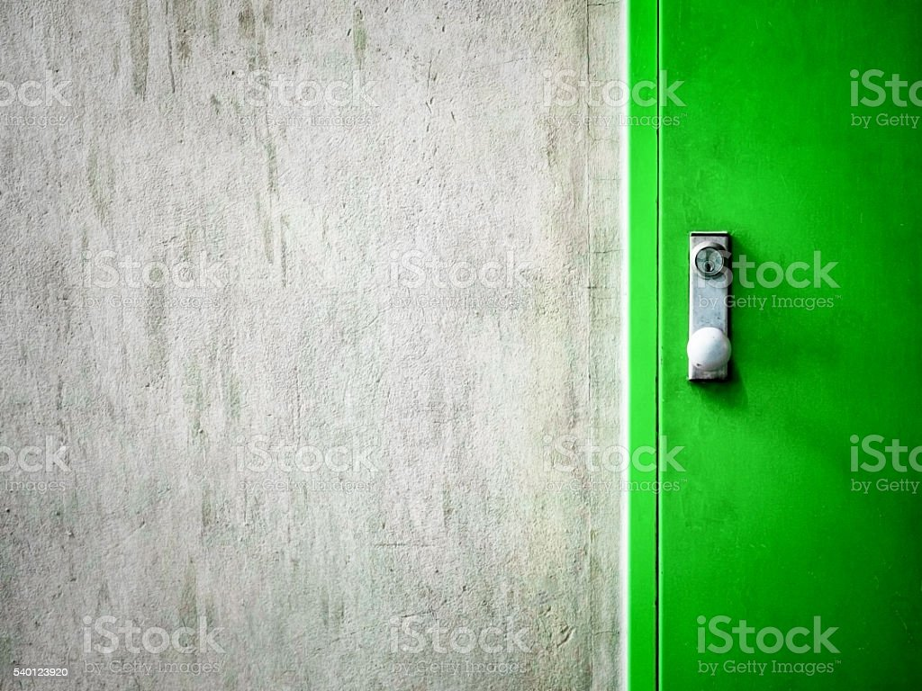 Cement concrete wall texture with modern green door. stock photo