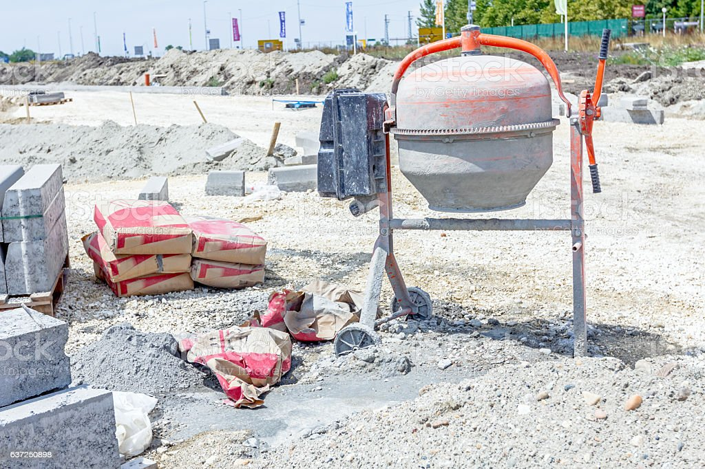 Cement mixer machine is at construction site with bags. stock photo