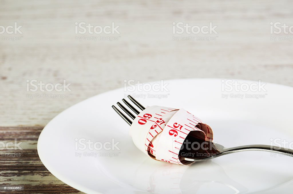centimeter reeled on  fork in  white plate on  wooden table stock photo