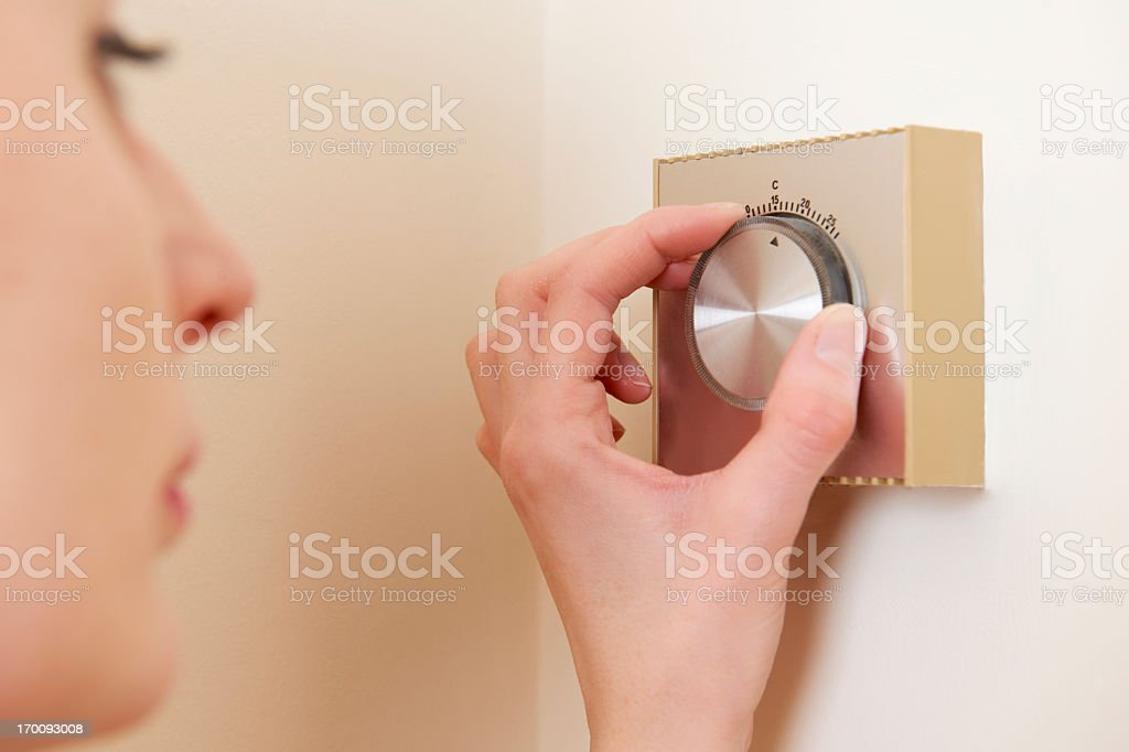 Central heating thermostat control on wall adjusted by woman royalty-free stock photo