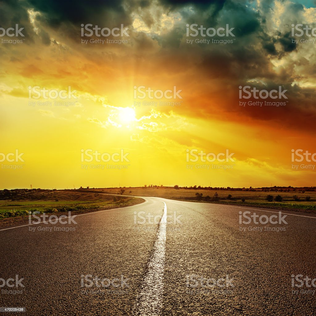 central white line on asphalt road and dramatic sunset stock photo