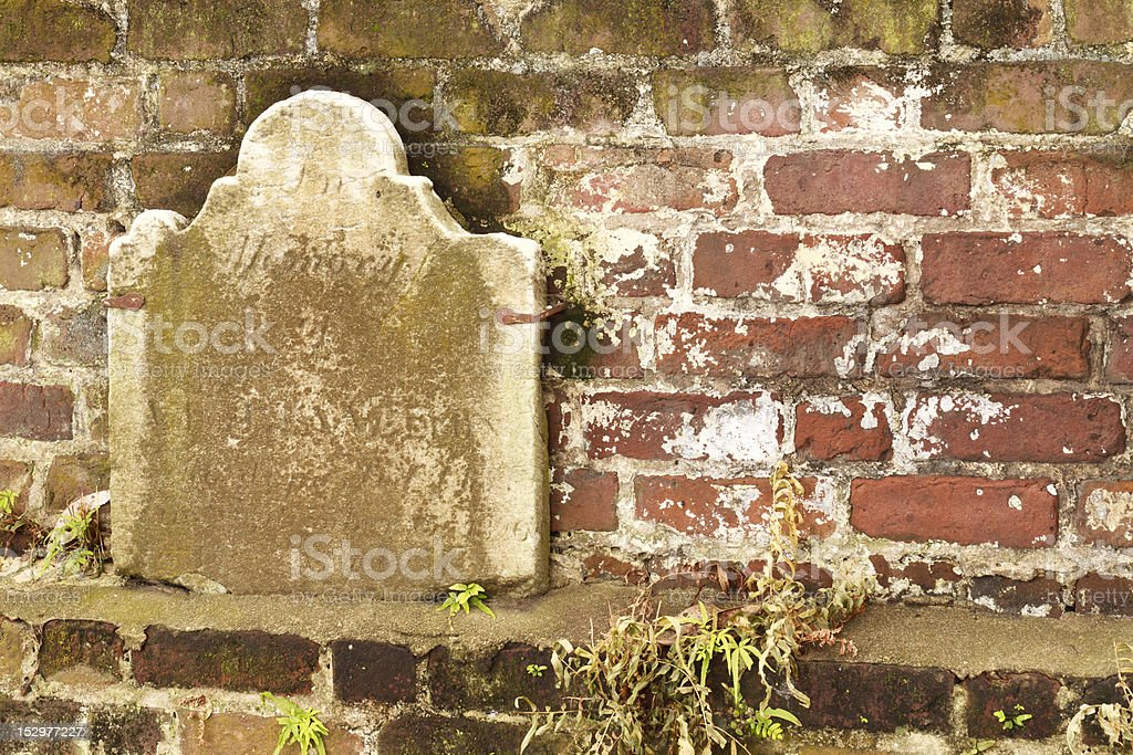Centuries Old Headstone Against Textured Wall stock photo