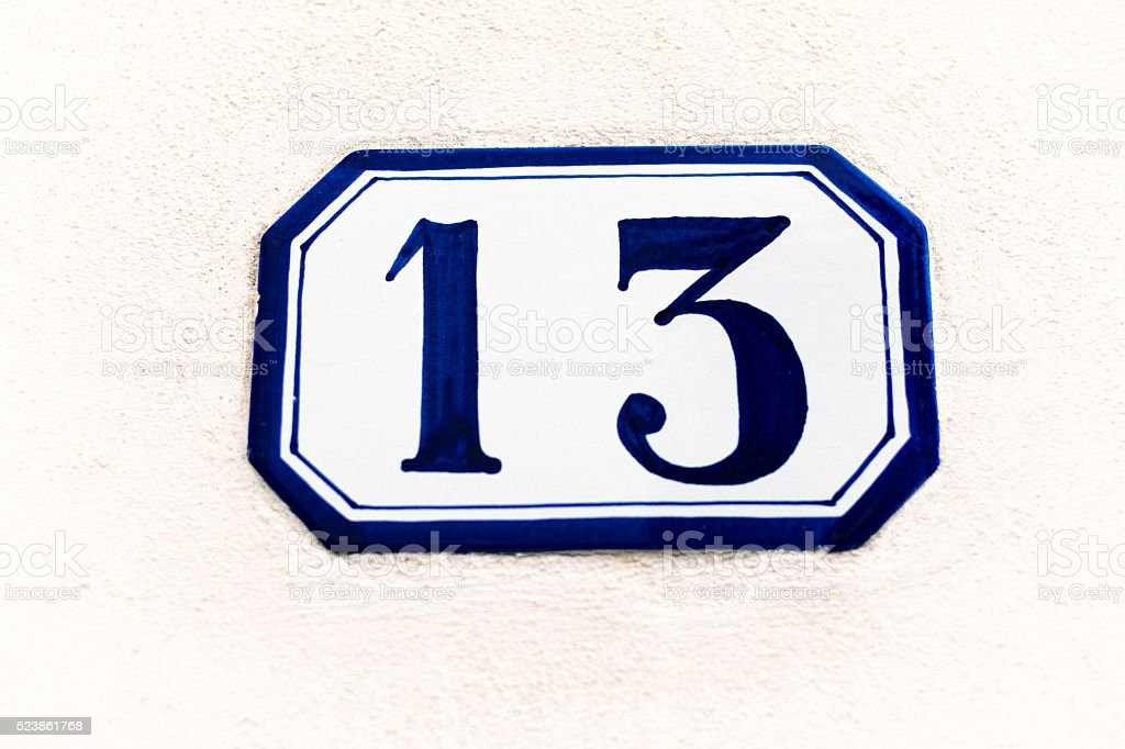 Ceramic Address Plaque Number 13 On White Wall stock photo
