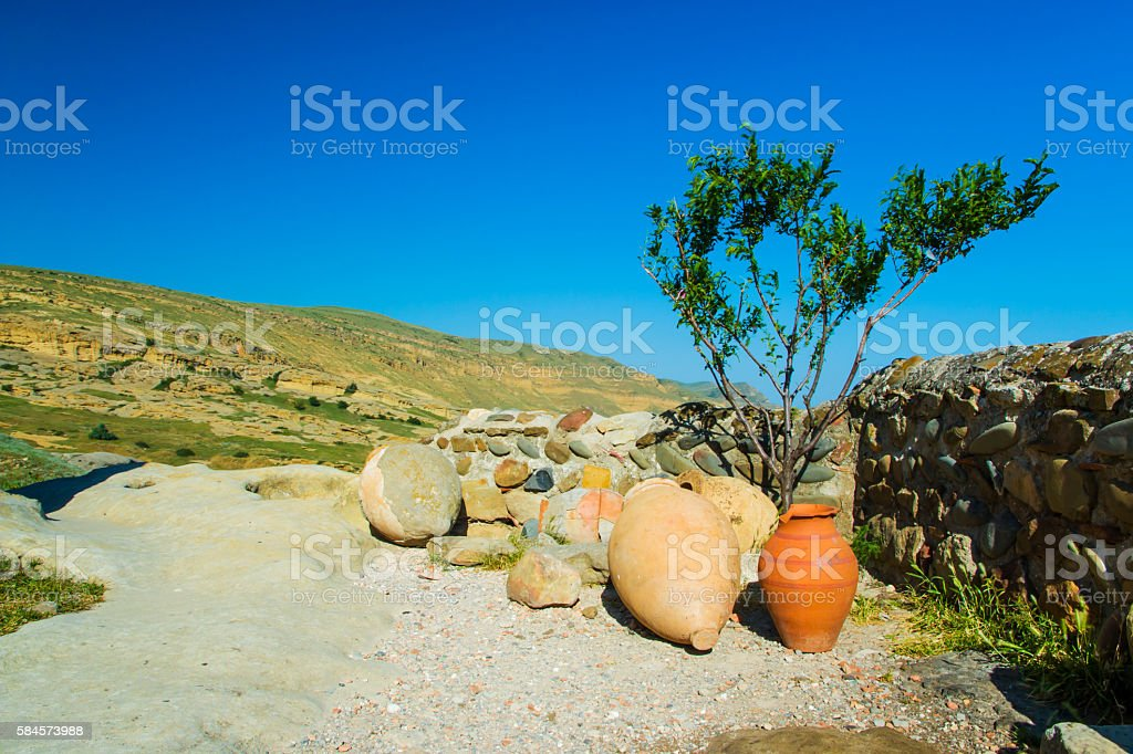 Ceramic ancient amphora for wine on  of mountains outdoors stock photo