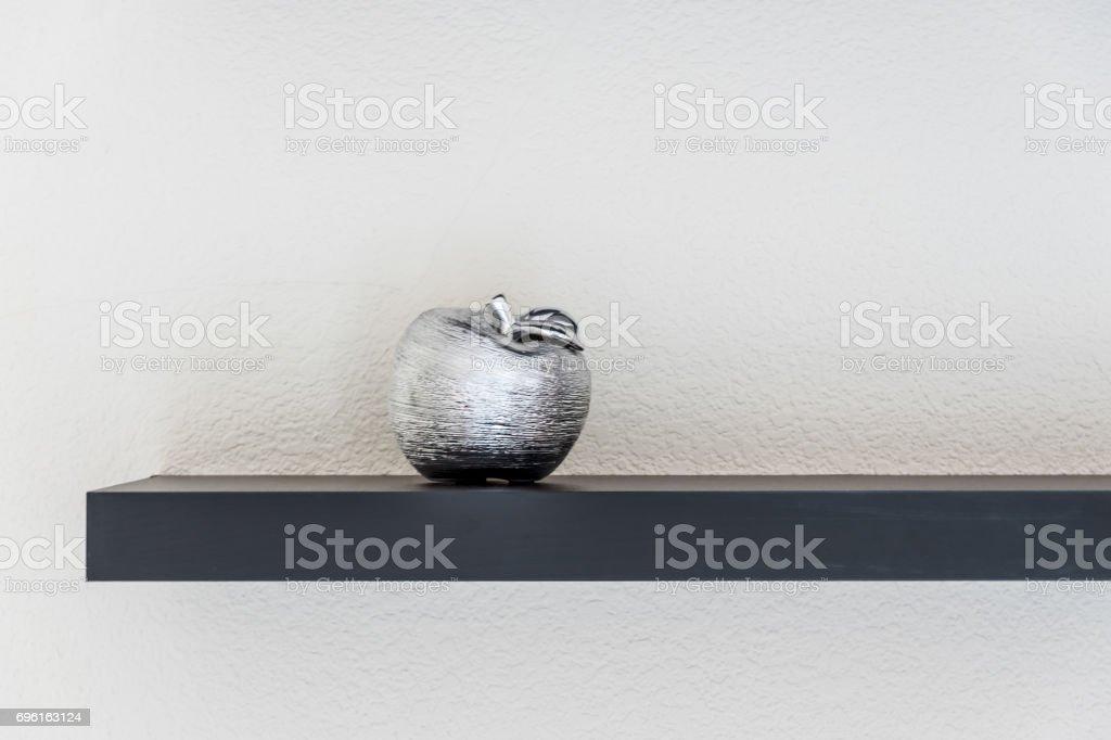 Ceramic apple on wooden shelf stock photo