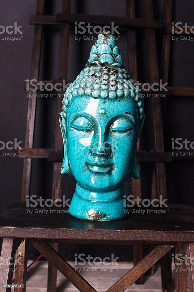 ceramic Buddha head old antique blue interior detail stock photo