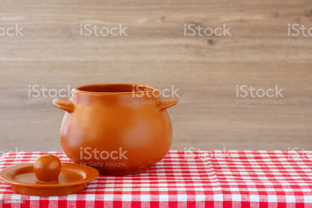 Ceramic pot with lid on a checkered tablecloth stock photo