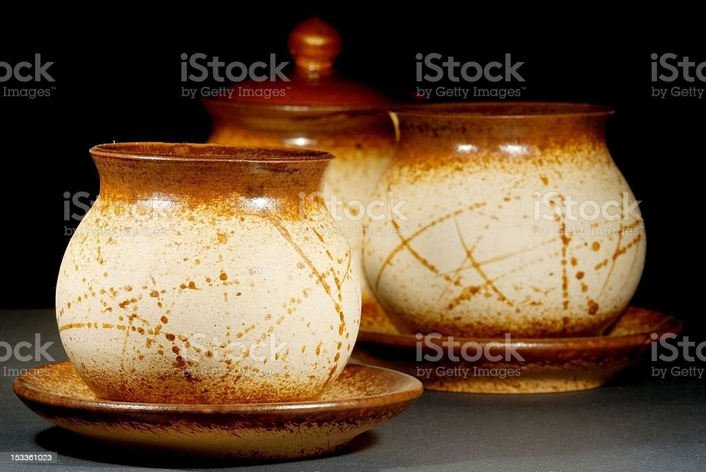 ceramic teapots with saucers on black background stock photo