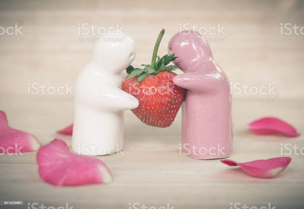 Ceramic toy giving a strawberry to couple for their love stock photo