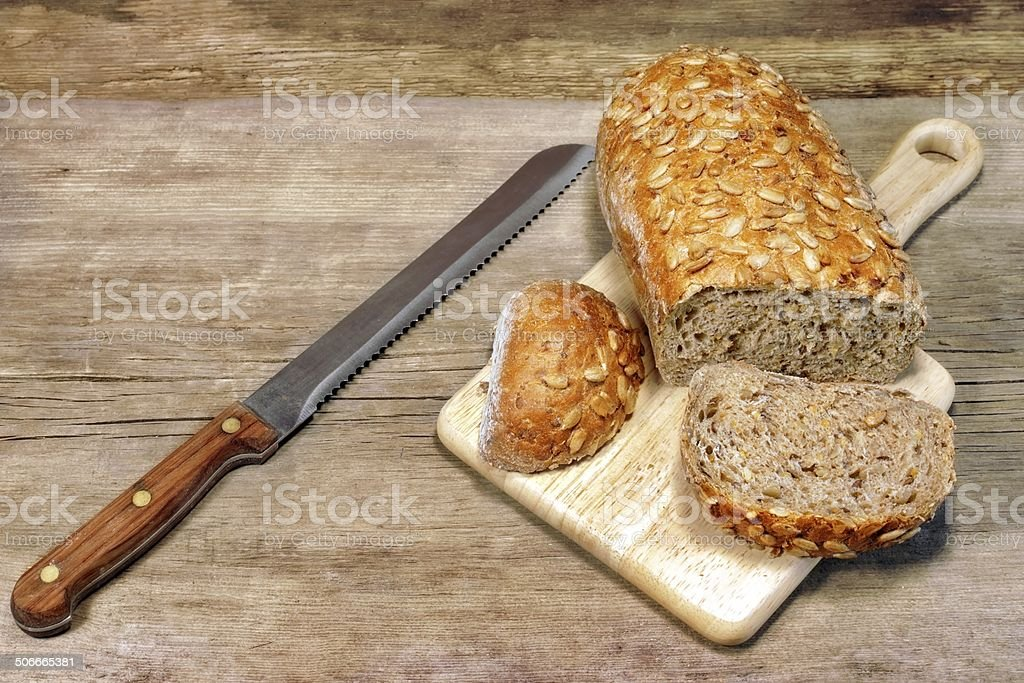 Cereal Bread Loaf with Grains and slicer knife stock photo