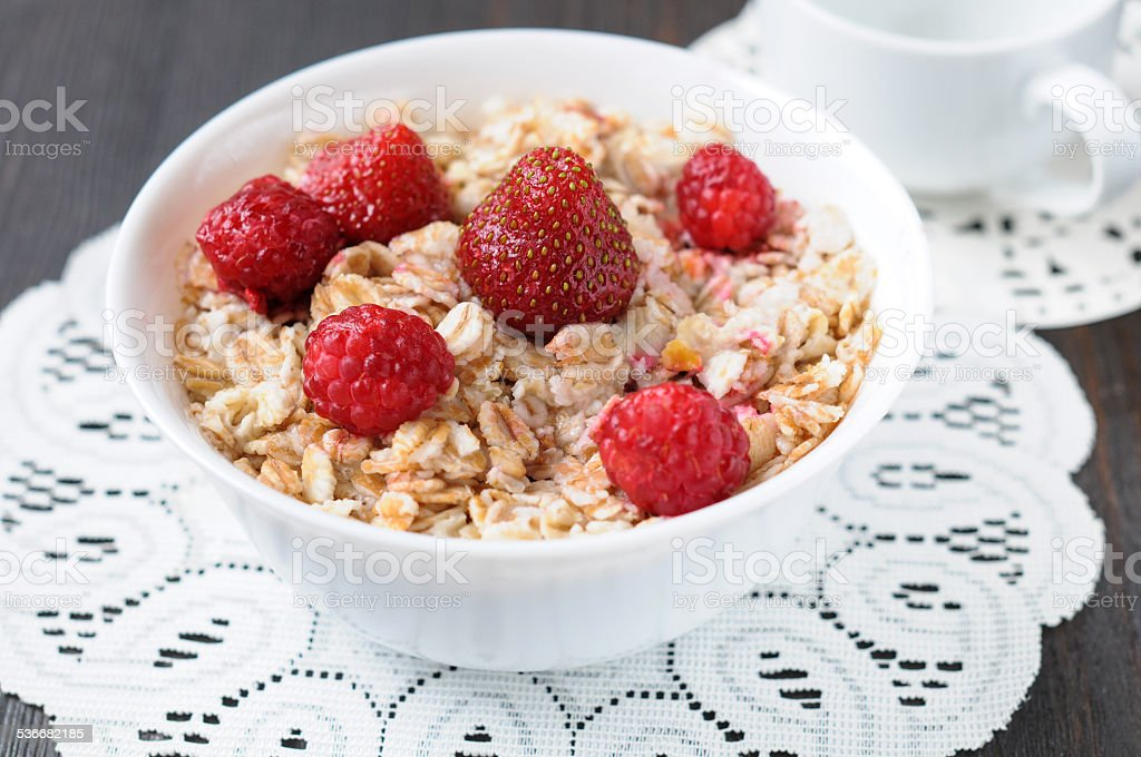 Cereal with fresh strawberries and raspberries for breakfast stock photo
