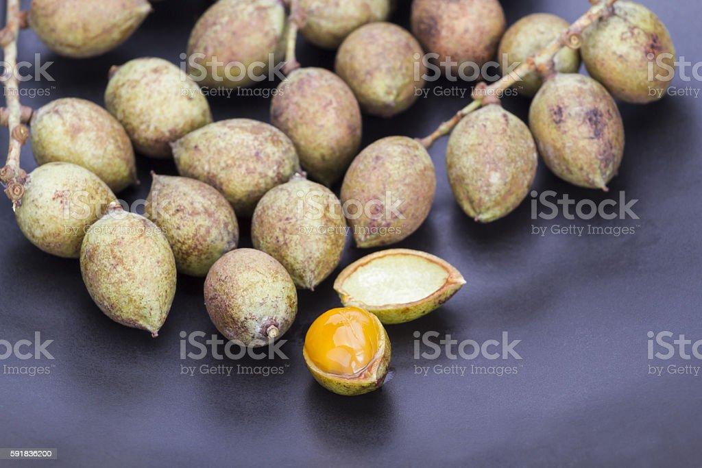 Ceylon oak fruit on black dish stock photo