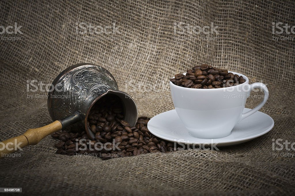 Cezve and cup with freshly roasted coffee beans on sackcloth royalty-free stock photo