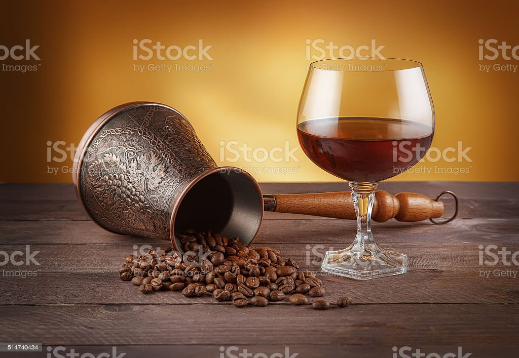 Cezve with coffee beans and glass of whiskey stock photo