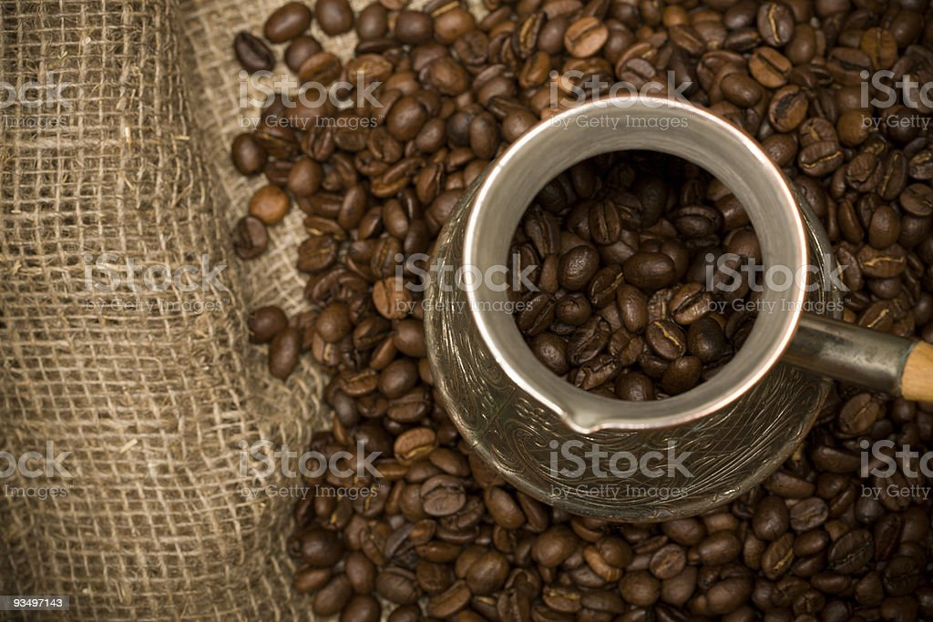 Cezve with freshly roasted coffee beans on sackcloth royalty-free stock photo